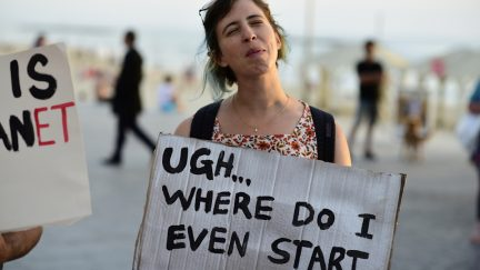 Woman holding sign that says,