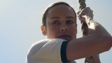 Brie Larson climbs a rope as Carol Danvers in Captain Marvel.
