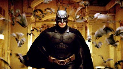 Christian Bale, flocked by bats, in Batman Begins.