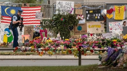 An armed police officer pauses by flowers and tributes near Al Noor mosque