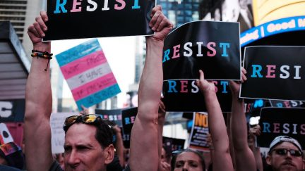Protesters hold signs reading RESIST, written in blue, pink and white, the colors of the transgender flag.
