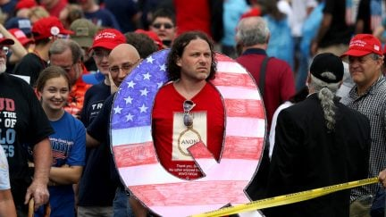 Trump supporter with a giant Q-shaped sign hanging around his neck looks sad and tired.