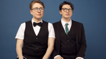 ser Malena-Webber and Aubrey Turner of The Doubleclicks sit side by side in suits.