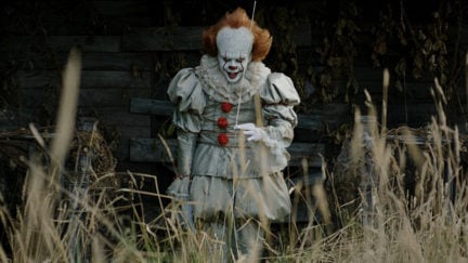 Pennywise (Bll Skarsgård) tries to catch a new victim in a still from IT: Chapter One.