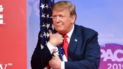 Donald Trump hugs a flag, presumably without its consent.