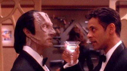 Bashir and Garak in formal wear as Bashir lifts a martini glass to Garak in Star Trek: Deep Space Nine.