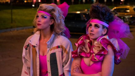 Debbie (Betty Gilpin) and Ruth (Alison Brie) stand on the street in bright pink 80s wrestling costumes.