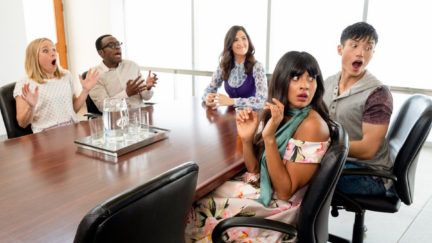 The characters of The Good Place sit at a table and looked surprised at something.