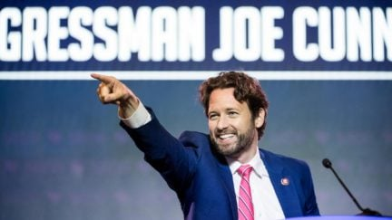 Joe Cunningham points to the crowd from a podium with his name projected behind him.