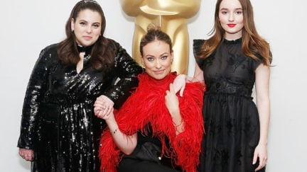 Actor Beanie Feldstein, actor, director and producer Olivia Wilde and actor Kaitlyn Dever pose in front of a life-size Oscar statue.