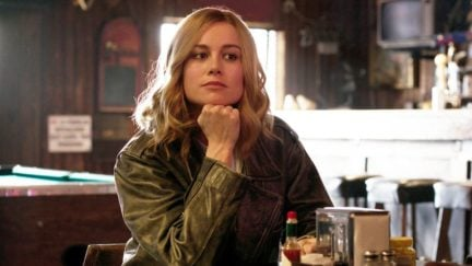 Captain Marvel sits with her head in her chin and a smirk.