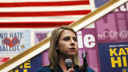 Katie Hill speaks to supporters in front of a number of progressive signs.