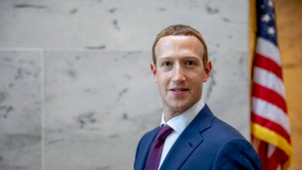 Mark Zuckerberg stands in front of an American flag looking surprised.