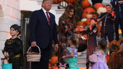 Donald Trump smiles awkwardly around children in Halloween costumes outside the White House.