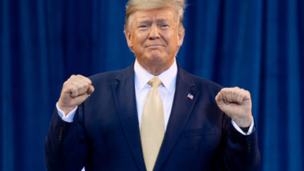Trump pumps his fists in front of a blue curtain.