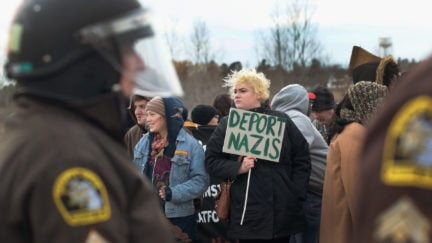 Anti-Nazi protester holds a sign saying