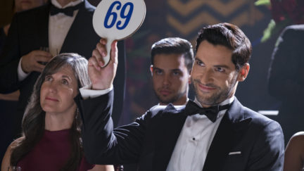 Lucifer holds up a auction paddle
