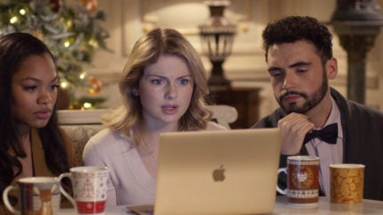 Amber and her friends from A Christmas Prince sit around her laptop looking concerned.