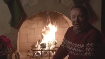 Kevin Spacey as Frank Underwood sits in front of a fireplace in a Christmas sweater, looking into the camera.
