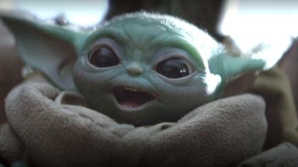 Baby Yoda with a wide-mouth smile in Disney+'s The Mandalorian Star Wars series.