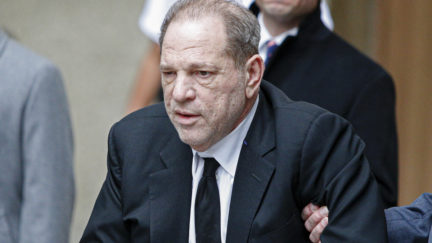 Harvey Weinstein leaves court as someone holds his arm.