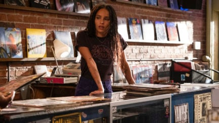 High Fidelity's Rob (Zoe Kravitz) leans on the counter of her record shop.