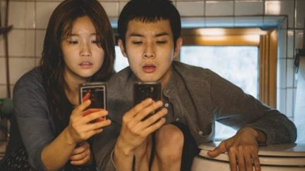 Characters from Parasite look at their phones in front of a toilet in their semi-basement apartment.