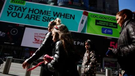 People walk past a sign that advises people to stay home in Times Square