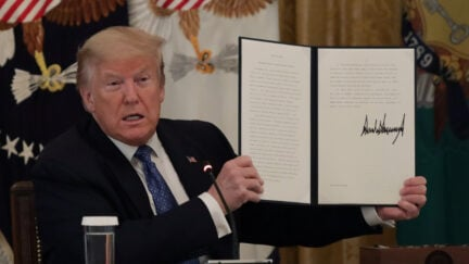 WASHINGTON, DC - MAY 19: U.S. President Donald Trump holds up a copy of an executive order he signed on DOT deregulation, during a meeting with his cabinet in the East Room of the White House on May 19, 2020 in Washington, DC. Earlier in the day President Trump met with members of the Senate GOP. (Photo by Alex Wong/Getty Images)