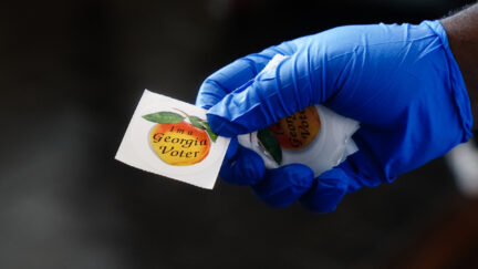 A gloved polling place worker holds an