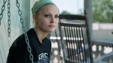 Daisy Coleman sits on her porch in a still from Audrie & Daisy.