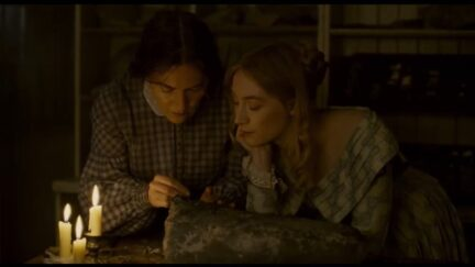kate winslet and saorise ronan look longingly at a rock and eachother