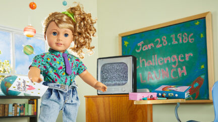 a sweet doll stands next to a black board touting the challenger launch