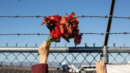 Activists from Yakima Immigrant Response Network wave flowers in front of a barbed wire fence.