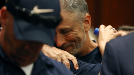 Jon Stewart gets a hug after the U.S. Senate voted to renew permanent authorization of September 11th Victim Compensation Fund
