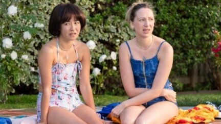 Anna and Maya from PEN15 sit in swimsuits at a pool party.