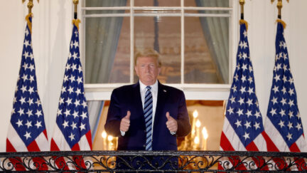Donald Trump gives a double thumbs up outside the White House with no mask on.