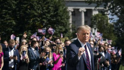 Donald Trump gestures as White House interns cheer him on as he leaves the White House residence