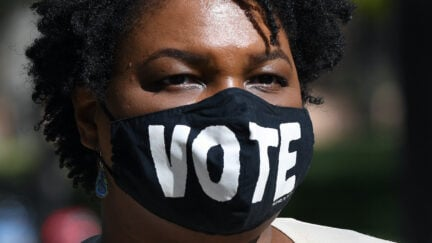 Stacey Abrams wears a face mask reading