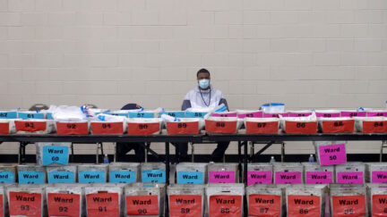 An election official sits behind a row of ballots to be recounted.