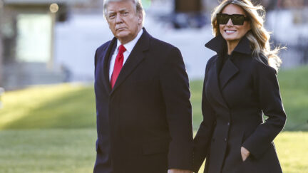 Donald and Melania Trump hold hands outdoors.
