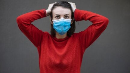 A person in a red sweater wearing a mask holds their head looking exasperated.
