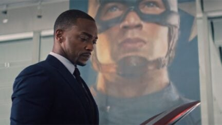 Sam Wilson looks at the Captain America Shield, standing in front of a banner with Steve Rogers' face.
