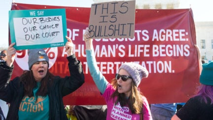 A pro-choice protester in a Planned Parenthood shirt holds a sign saying