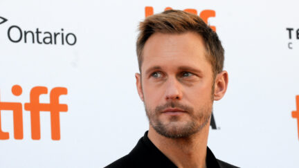 Alexander Skarsgård looks to the side in front of a wall featuring the TIFF logo.