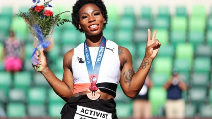 Gwen Berry smiles holding a bouquet of flowers and flashes a peace sign, wearing a bronze medal around her neck and a shirt tied around her waist reading