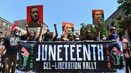 Protestors hold pictures of George Floyd as they march during a Juneteenth rally