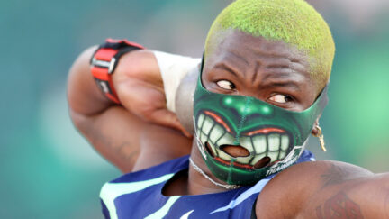 Raven Saunders wears a Hulk mask with dyed green shaved hair while throwing a shot put during the Olympic trials.