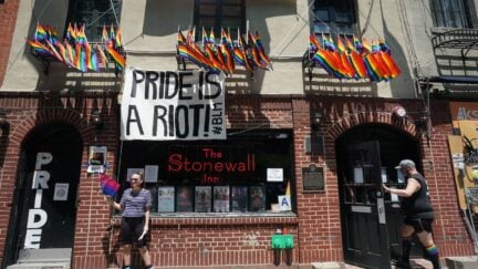 The Stonewall Inn in New York flies LGBTQIA flags and a sign reading