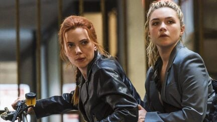 Scarlett Johansson as Natasha Romanoff and Florence Pugh as Yelena Belova sit together on a motorcycle in the movie 'Black Widow'